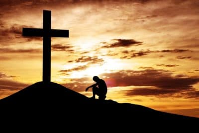 Christian Kneeling at Cross on a Hill